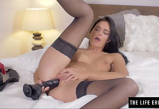 Shaved beauty pushes a fat black dildo inside