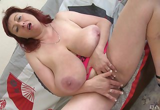 Redhead chick squeezes her boobs while sucking on a dildo